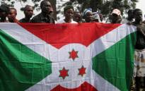 Burundian refugees who voluntarily came back to Burundi from the Democratic Republic of Congo (DRC) pose with a Burundian flag in the western Burundian town of Gatumba on 5 October 2010. Picture: AFP.