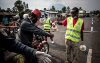 FILE: A motor taxi driver gets his hands washed at an Ebola screening station on the road between Butembo and Goma on 16 July 2019 in Goma. Picture: AFP