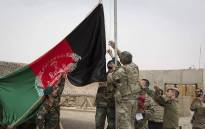This handout photograph taken on 2 May 2021 and released by Afghanistan's Ministry of Defense shows US soldiwrs and Afghan National Army (ANA) soldiers rising Afghanistan's national flag uring a handover ceremony to the Afghan National Army (ANA) army 215 Maiwand corps at Antonik camp in Helmand province. Picture: Afghanistan's Ministry of Defence office/AFP
