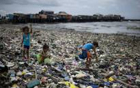 FILE: Children collect plastic bottles in Manila Bay in the Philippines. Picture: AFP.