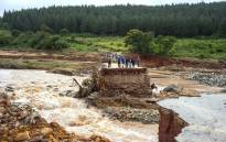 FILE: Timber company workers stand stranded on a damaged road on 18 March 2019, at Charter Estate, Chimanimani, eastern Zimbabwe, after the area was hit by the cyclone Idai.  Picture: AFP
