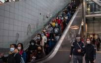 People wearing protective face masks use an escalator in Hong Kong on 9 February 2020, as a preventative measure after a coronavirus outbreak which began in the Chinese city of Wuhan. Picture: AFP