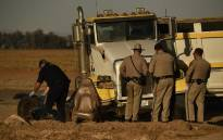 Investigators and California Highway Patrol Border Division officers look over the scene of a crash between an SUV and a semi-truck full of gravel near Holtville, California on March 2, 2021. Picture: Patrick T. Fallon / AFP.