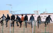 In this file photo taken on February 19, 2015 migrants sit atop a border fence separating Morocco from the north African Spanish enclave of Melilla in the first attempt to jump since the camp on Mount Gurugu burned down. Picture: AFP.