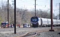 Emergency personnel investigate the crash site of Amtrak Palmetto train 89 on April 3, 2016 in Chester, Pennsylvania. Two people are confirmed dead after the lead engine of the train struck a backhoe that was on the track sourth of Philadelphia, according to published reports. Approximately 341 passengers and seven crew members were onboard the train, which was traveling from New York to Savannah, according to Amtrak. Picture: AFP.