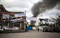 Electoral banners are seen as smoke rises from a fire at the independent national electoral commission's (CENI) warehouse on 13 December 2018 in Kinshasa, ten days ahead of presidential elections that have been foreshadowed by violence. Picture: AFP