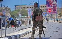 FILE: A member of Somalia's security services patrols the scene of a suicide car bomb blast in Mogadishu. Picture: AFP