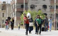 Syrian civilians from the town of Daraya are evacuated from the rebel-held town of Moadamiyet al-Sham on 8 September, 2016 to be taken to a shelter in the government-controlled town of Harjala. Picture: AFP.