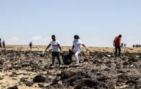 Rescue team carry collected bodies in bags at the crash site of Ethiopia Airlines near Bishoftu, town some 60 kilometres southeast of Addis Ababa, Ethiopia, on 10 March 2019. Picture: AFP