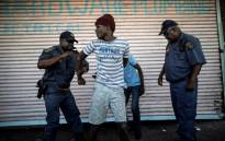A suspected looter is detained by South African police officers as he emerges from of a looted foreign-owned shop in Soweto, Johannesburg, on 29 August, 2018 during unrest that erupted after a foreign shop owner allegedly shot and killed a member of the community during a demonstration. Picture: AFP.
