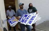 General Motors Co. employee Carl Ellison carries strike signs outside of the United Auto Workers (UAW) Local 163 which represents GM's Romulus Powertrain on 15 September 2019 Picture: AFP