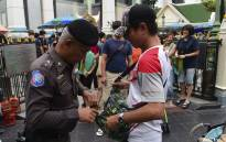 A Thai policeman searches a visitor's bag at the Erawan Shrine in the centre of Bangkok on August 13, 2016 as authorities increase security following a new string of bomb attacks in Thailand. Picture: AFP.