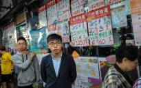 Pro-democracy activist Joshua Wong (C), who was disqualified from running, queues up to cast his vote during district council elections in the South Horizons district in Hong Kong on 24 November 2019. Picture: AFP