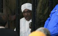 FILE: Sudan's deposed military ruler Omar al-Bashir sits in a defendant's cage during his corruption trial in Khartoum on 24 August 2019. Picture: AFP