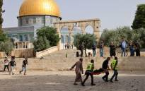 Palestinian medics walk near the Dome of the Rock as they evacuate on a stretcher a wounded protester from the Aqsa mosque compound in Jerusalem's Old City on 10 May 2021, amidst clashes with Israeli security forces.Picture: Ahmad Gharabli/AFP