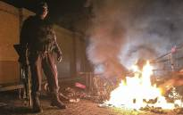 A police officer stands next to a burning shopping trolley as he looks for looters outside the Central City shopping centre in Mabopane north of Pretoria on 23 June 2016. Picture: Reinart Toerien/EWN.