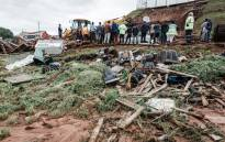 Police officers try to rescue people trapped in their homes destroyed in a mudslide following torrential downpours and flash floods, near Westcliff Secondary School in Chatsworth, south of Durban on 23 April 2019. Picture: AFP