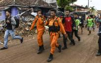 """Members of an Indonesian search and rescue team carry the body of a victim, retrieved from a collapsed home, in a body bag in Rajabasa in Lampung province on 25 December 2018, three days after a tsunami - caused by activity at a volcano known as the """"child"""" of Krakatoa - hit the west coast of Indonesia's Java island. Picture: AFP"""