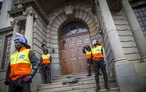 FILE: University of the Free State campus security stand guard at the doors to the main building which were vandalised during protests. Picture: Reinart Toerien/EWN.
