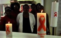 Health workers observing World AIDS Day, posing behind candles commemorating. Picture: AFP.