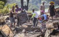 FILE: Residents of the Imizamo Yethu informal settlement in Hout Bay, Cape Town, help to clear the rubble after a fire ripped through a section. Picture: Aletta Harrison/EWN.