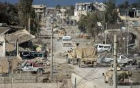 Vehicles belonging to the US-led coalition drive down a street in the frontline Syrian village of Baghuz, on 17 February 2019. Picture: AFP
