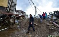 FILE: Residents walk past mud and flood-damaged homes in Nagano on 15 October 2019, after Typhoon Hagibis hit Japan on 12 October 2019. Picture: AFP