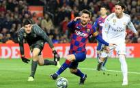 "FILE: Real Madrid's Spanish defender Sergio Ramos (R) challenges Barcelona's Argentine forward Lionel Messi (C) next to Real Madrid's Belgian goalkeeper Thibaut Courtois during the ""El Clasico"" Spanish League football match between Barcelona FC and Real Madrid CF at the Camp Nou Stadium in Barcelona on 18 December 2019. Picture: AFP."