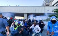 Protestors run for cover after police fire stun grenades to disperse them during a protest at the Cape Town Civic Centre on 19 November 2020. Picture: Kaylynn Palm/EWN