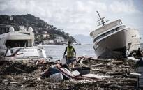FILE: A man walks through garbage between two yachts after a storm hit the harbour and destroyed a part of the dam on 30 October 2018 in Rapallo, near Genoa, Italy. Picture: AFP.