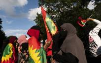 People hold Oromo flags as they gather outside the Governor's Mansion to protest the death of musician and activist Hachalu Hundessa on 30 June 2020 in St Paul, Minnesota. Hundessa, was shot and killed in Addis Ababa, Ethiopia on 29 June. Picture: AFP