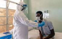 FILE: A medical staff member wearing protective equipment places a face mask on a mock patient at the Wilkins Infectious Diseases Hospital in Harare. Picture: AFP