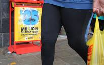 A woman walks past a lotto stand in Pretoria. Picture: EWN