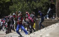 FILE: Students throw stones at private security guards during clashes at the University of Witwatersrand during Fees Must Fall protests on 10 October 2016. Picture: AFP