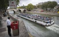 A man stands at a public urinal on 13 August 2018, on the Saint-Louis island in Paris, as a tourist barge cruises past. Picture: AFP.
