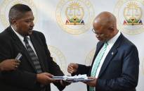 Chief Justice Mogoeng Mogoeng receives the lists of designated members of Parliament and members of provincial legislatures from IEC chairperson Glen Mashinini. Picture: @GovernmentZA/Twitter