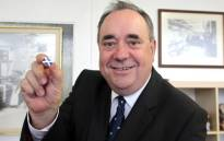 Alex Salmond, Scotland's leader of the Scottish National Party (SNP) and first minister, holds a pin with the Scottish flag during a visit to the Barrie Knitwear factory in Hawick, Scotland. Picture: AFP/Graham Stuart
