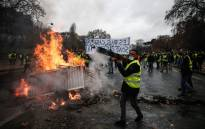 Protesters build a barricade during a protest of yellow vests against rising oil prices and living costs, on 1 December, 2018 in Paris. Picture: AFP