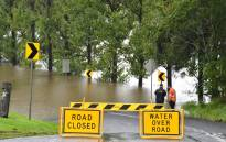 Workers look at an inundated main road by floodwaters in Richmond suburb on 22 March 2021, as Sydney braced for its worst flooding in decades after record rainfall caused its largest dam to overflow and as deluges prompted mandatory mass evacuation orders along Australia's east coast. Picture: Saeed Khan/AFP