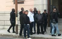 Nafiz Modack, pictured wearing a white shirt, is surrounded by security personnel outside the Cape Town Regional Court on 16 April 2019. Picture: Shamiela Fisher/EWN.