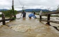 Men wade through a flooded area in the central province of Nghe An, Vietnam. At least 37 people have died and another 40 are missing after floods and landslides ravaged northern and central Vietnam, disaster officials said on October 12. Picture: AFP