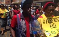"""A student shouts """"free water"""" as peers keep each other hydrated in blazing heat in Pretoria during the Fees Must Fall march. They're making their way to the Union Buildings where President Jacob Zuma will be addressing student leaders and vice-chancellors. Picture: EWN."""