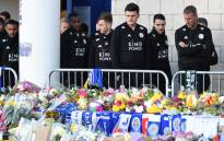 (L-R) Leicester City's English defender Danny Simpson, Leicester City's English-born Jamaican defender Wes Morgan, Leicester City's English midfielder James Maddison, Leicester City's English defender Harry Maguire, Leicester City's English midfielder Matty James and goalkeeping coach Mike Stowell look at the floral tributes left to the victims of the helicopter crash which killed Leicester City's Thai chairman Vichai Srivaddhanaprabha, outside Leicester City Football Club's King Power Stadium in Leicester, eastern England, on 29 October 2018. Picture: AFP.