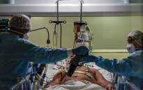Health workers wearing protective suits check a COVID-19-infected patient in intensive care unit, at the Emilio Ribas hospital in Sao Paulo, Brazil on 20 April 2020. Picture: AFP