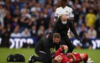 A trainer runs on the pitch to help Liverpool midfielder Harvey Elliott (R) after he suffered a serious leg injury following a tackle by Leeds United defender Pascal Struijk (not seen) during the English Premier League football match between Leeds United and Liverpool at Elland Road in Leeds, northern England on 12 September 2021. Picture: Oli Scarff/AFP