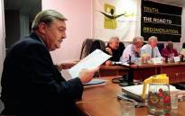 FILE: Pik Botha, former South African foreign minister, goes through his notes while members of the Truth and Reconciliation Commission board are in discussion during hearings in Johannesburg on 14 October 1997. Picture: AFP