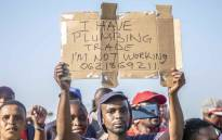 Cosatu supporter holding up a poster at the federation's May Day rally at Sugar Ray Xulu stadium in Clermont, Durban. Picture: Abigail Javier/EWN