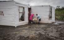Two women pour out mudwater from their shack after it was wrecked by heavy rains on the N17, Ga Rankuwa, North of Pretoria. Picture: Sethembiso Zulu/EWN