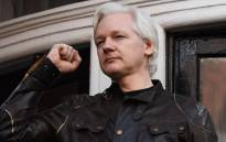 In this file photo taken on 19 May 2017, Wikileaks founder Julian Assange raises his fist prior to addressing the media on the balcony of the Embassy of Ecuador in London. Picture: AFP