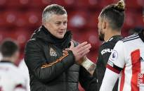 Manchester United manager Ole Gunnar Solskjaer (L) congratulates defender Alex Telles after the English Premier League football match between Sheffield United and Manchester United at Bramall Lane in Sheffield, northern England on 17 December 2020. Picture: AFP
